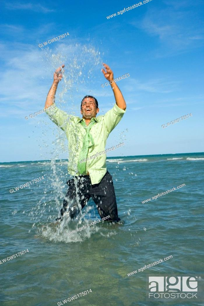 Stock Photo: Mid adult man splashing water in the sea.