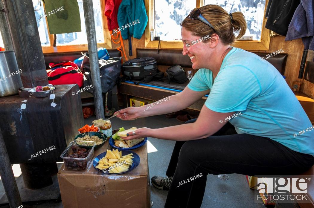 Photo de stock: A visitor preparing lunch at the Don Sheldon Mountain House in the Ruth Ampitheater in the Alaska Range, interior Alaska, Summer.
