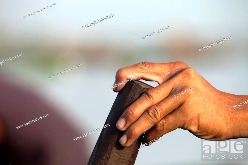 Stock Photo: Detail of a fisherman's hand at work on the Mekong River early in the morning outside of Phnom Penh, Cambodia.