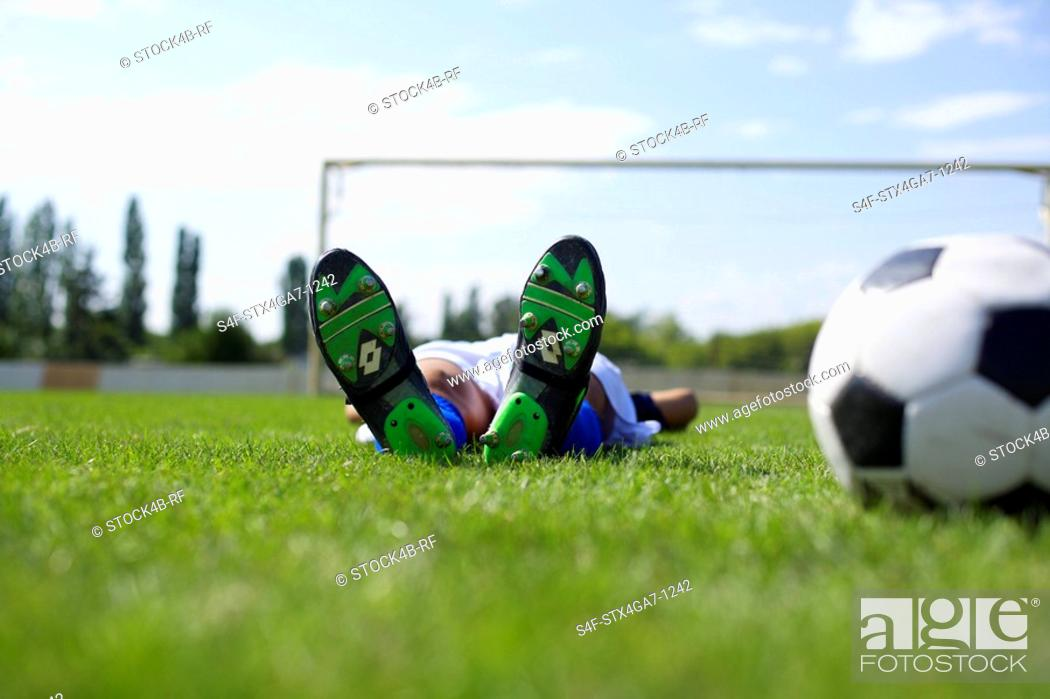 Stock Photo: Exhausted kicker lying on grass.