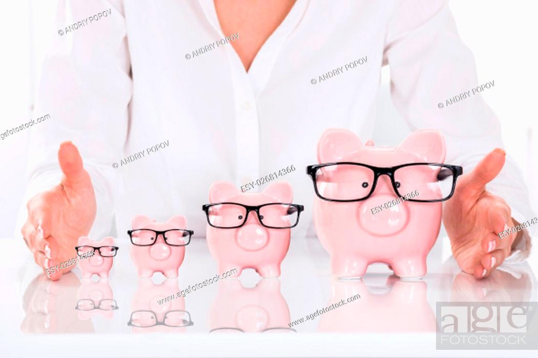 Stock Photo: Close-up Of Person's Hand Protecting Piggybanks On Desk.