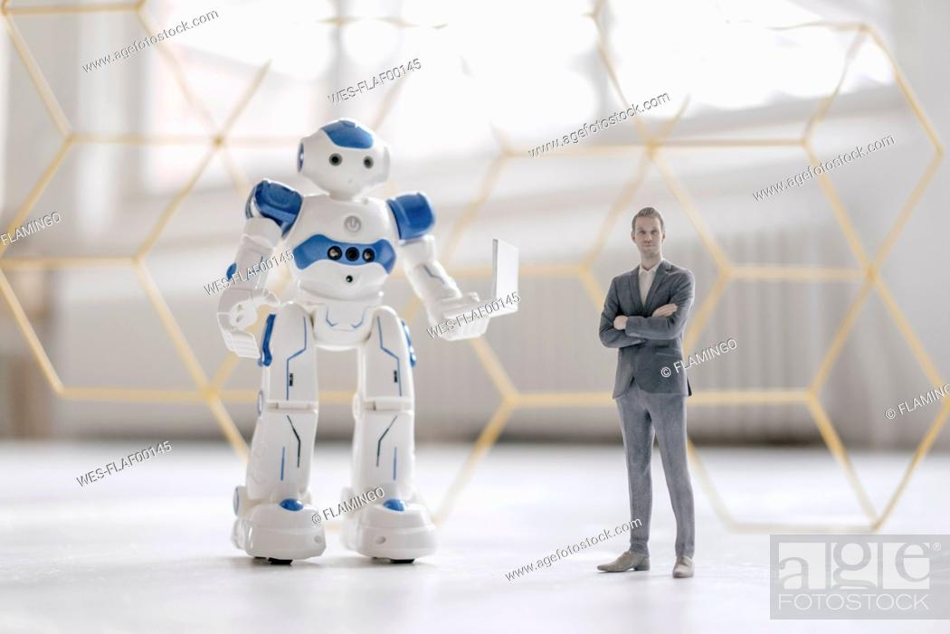 Stock Photo: Miniature businessman figurine standing next to robot with laptop.