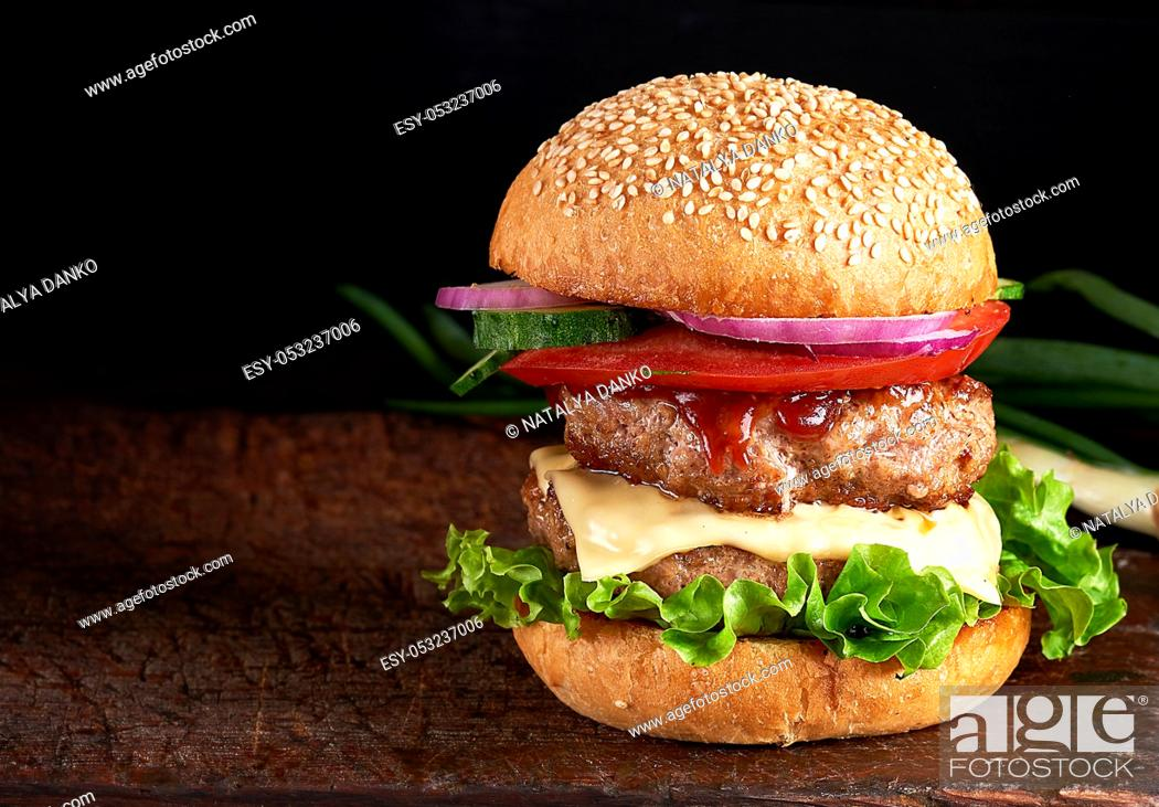 Stock Photo: large burger with two fried cutlets, cheese and vegetables in a round wheat flour bun, copy space.