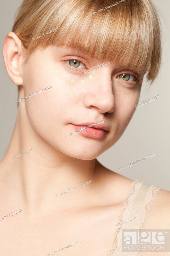 Stock Photo: Portrait of young woman wearing make up dotted under eye.