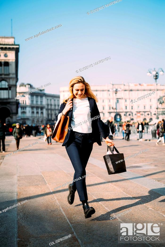 Stock Photo: Young female tourist with shopping bags strolling in city square, Milan, Italy.