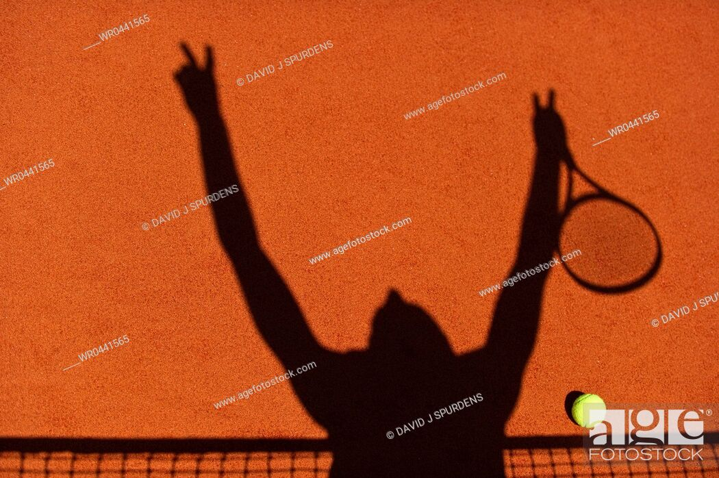 Stock Photo: The silhouette of a tennis player celebrating at the net.