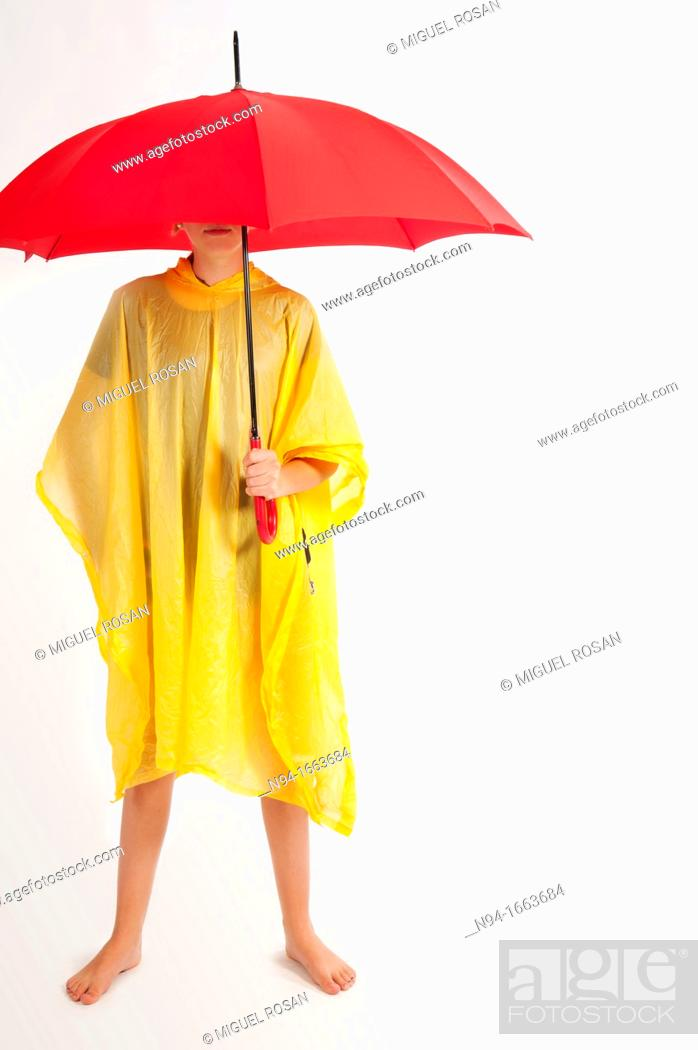 Stock Photo: Teenage girl with yellow rain gear protected with red umbrella.