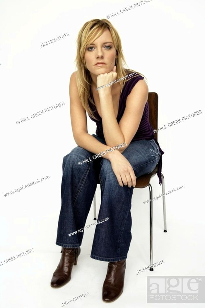 Stock Photo: Young woman sitting in chair.