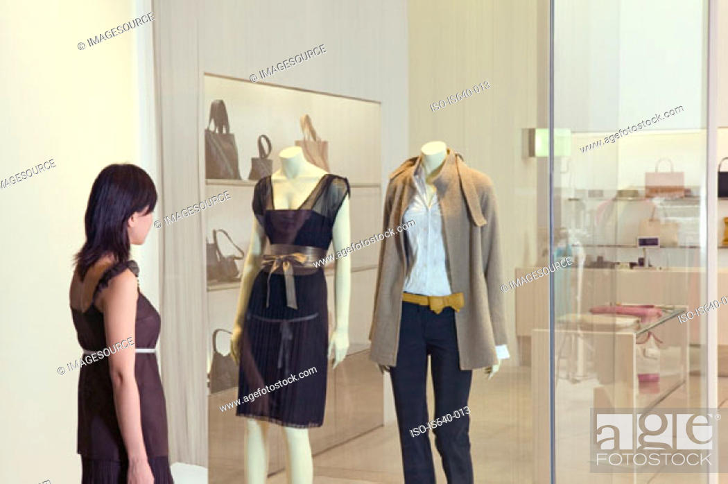 Stock Photo: Woman looking in clothes store window.