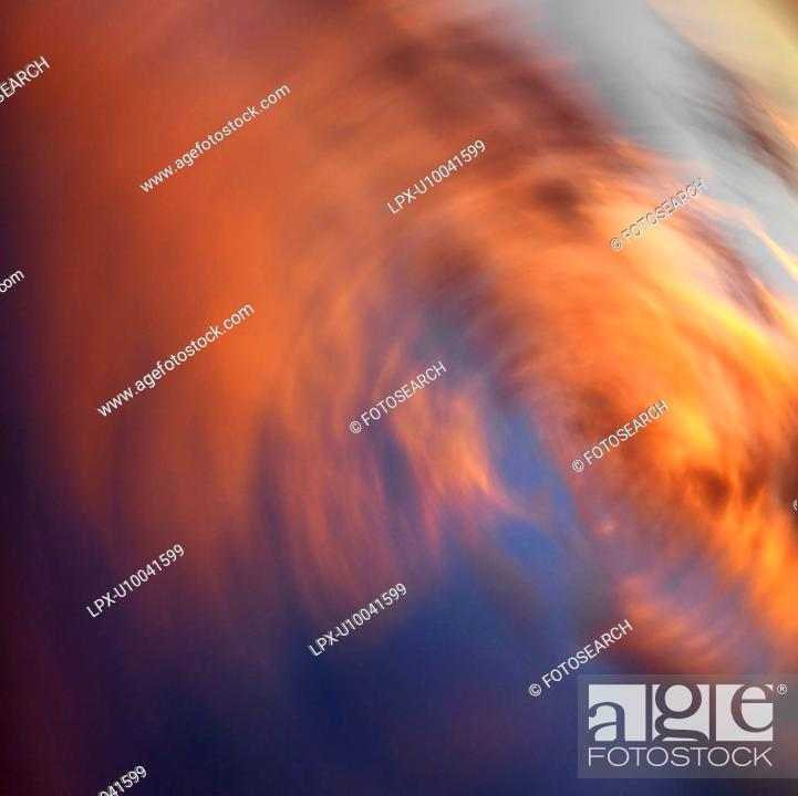 Stock Photo: Spiral orange clouds in sky with sunset.