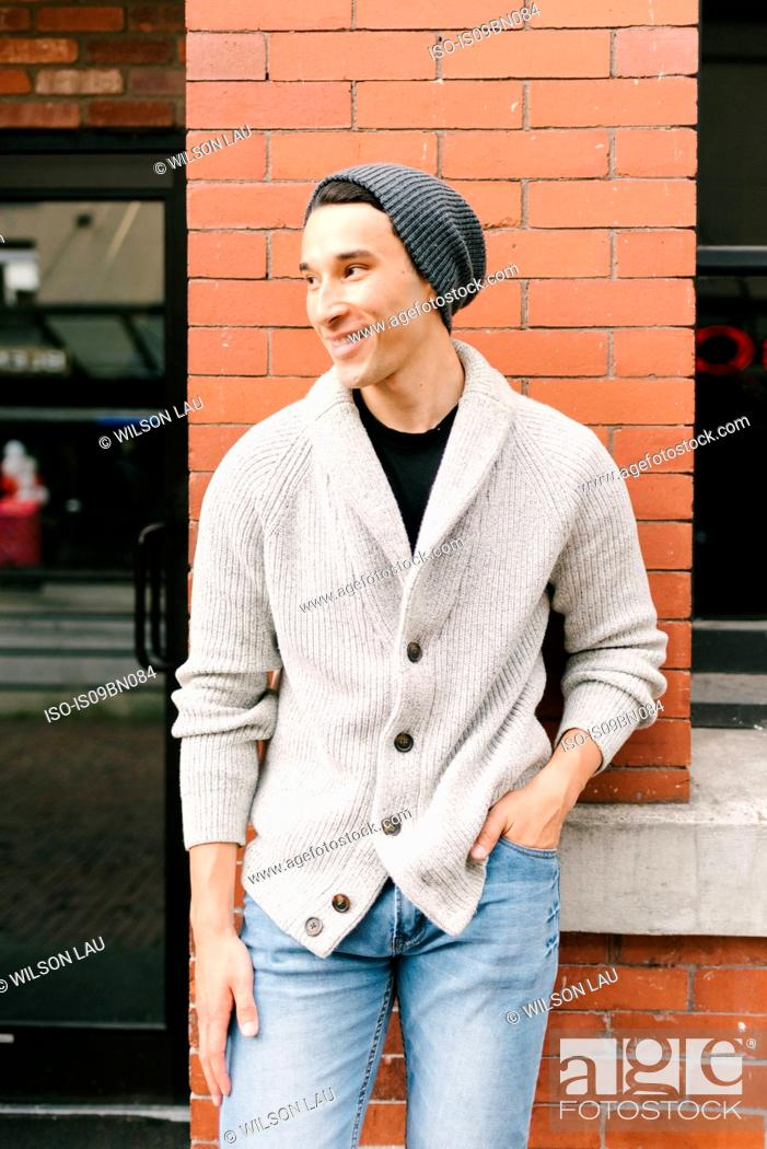 Stock Photo: Young man leaning against brick wall, Vancouver, Canada.