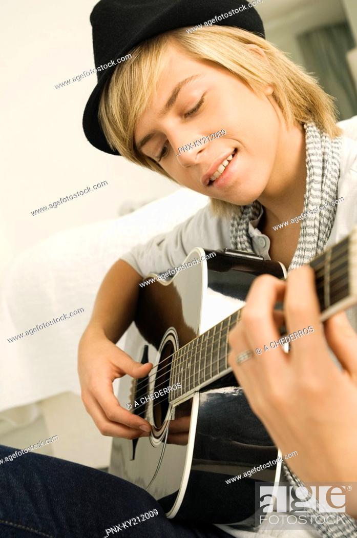 Stock Photo: Teenage boy playing a guitar.