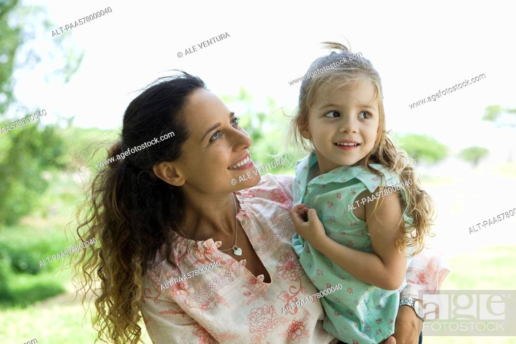 Stock Photo: Mother holding young daughter outdoors.