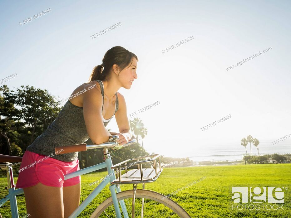 Stock Photo: Young woman with bicycle in park.