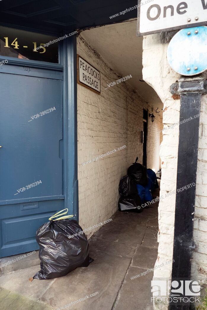 Imagen: Marine blue door leading to Peacocks Passage ironically full of rubbish sacks and waste, Rochdale, Yorkshire, England, UK.