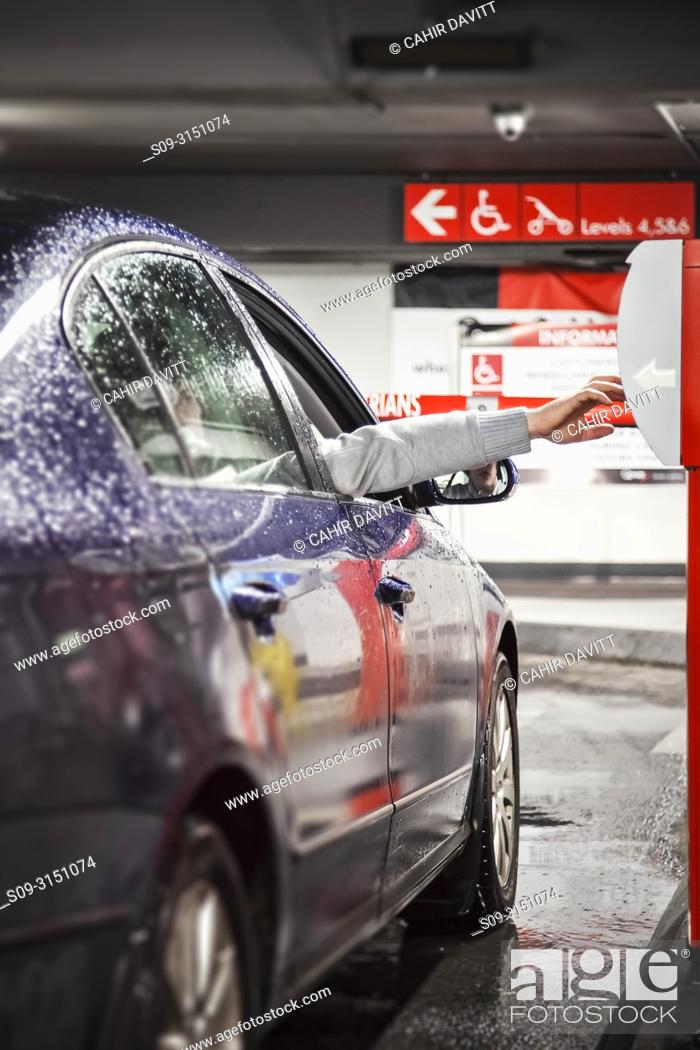Stock Photo: A customer takes a ticket in the interior of Q-Park Eyre Square car park, Galway, Co. Galway, Ireland.