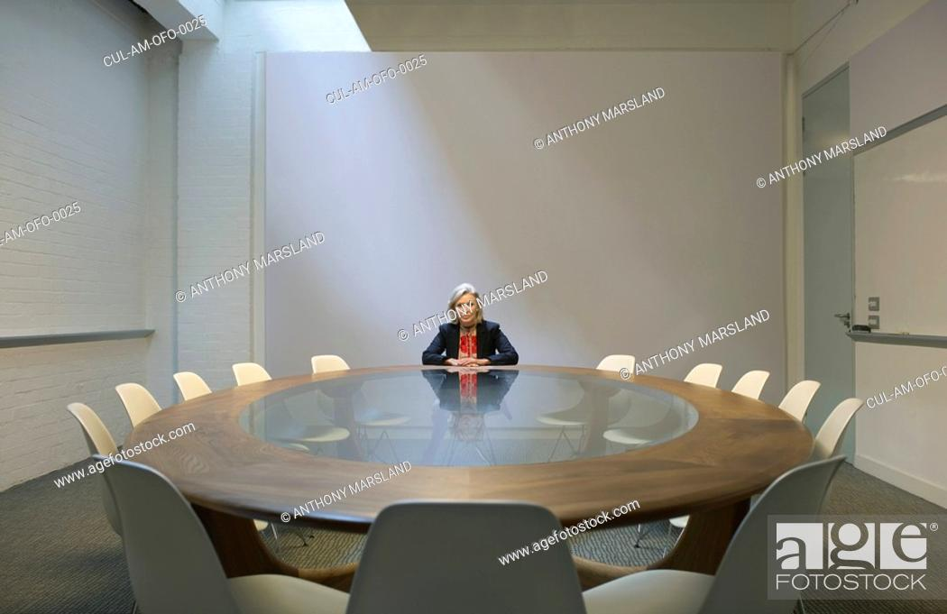 Stock Photo: Woman seated in boardroom alone.