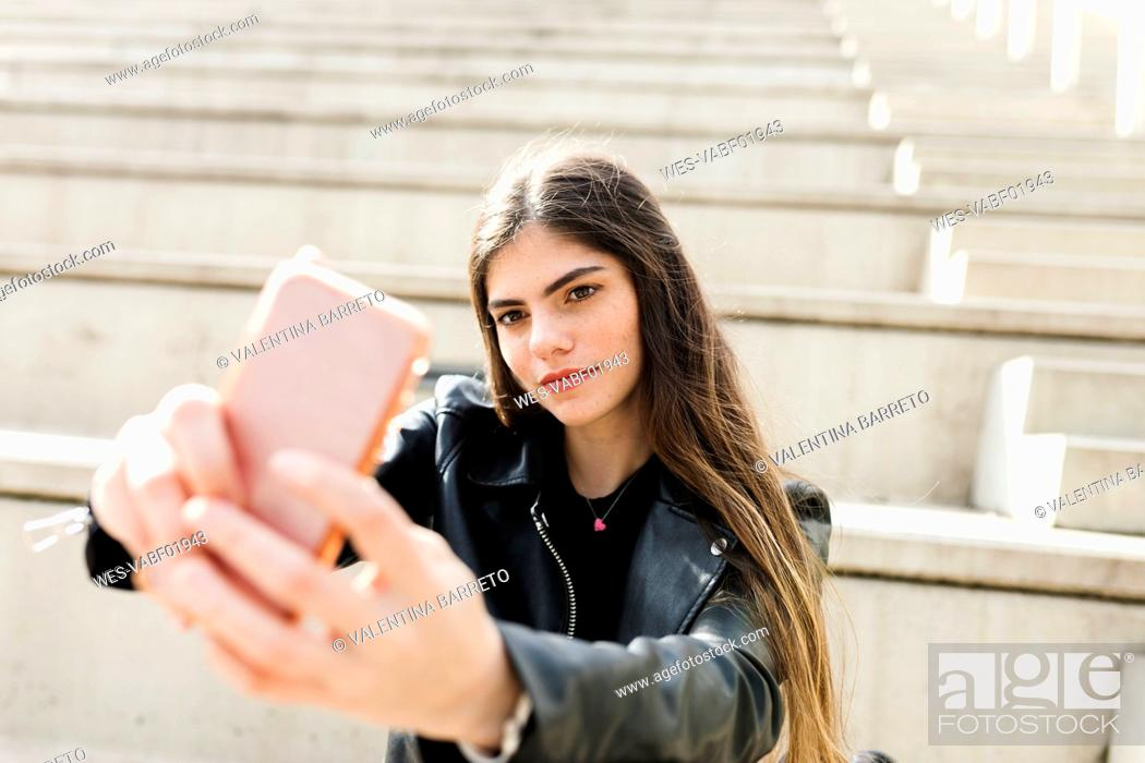 Stock Photo: Young woman on stairs taking a selfie.