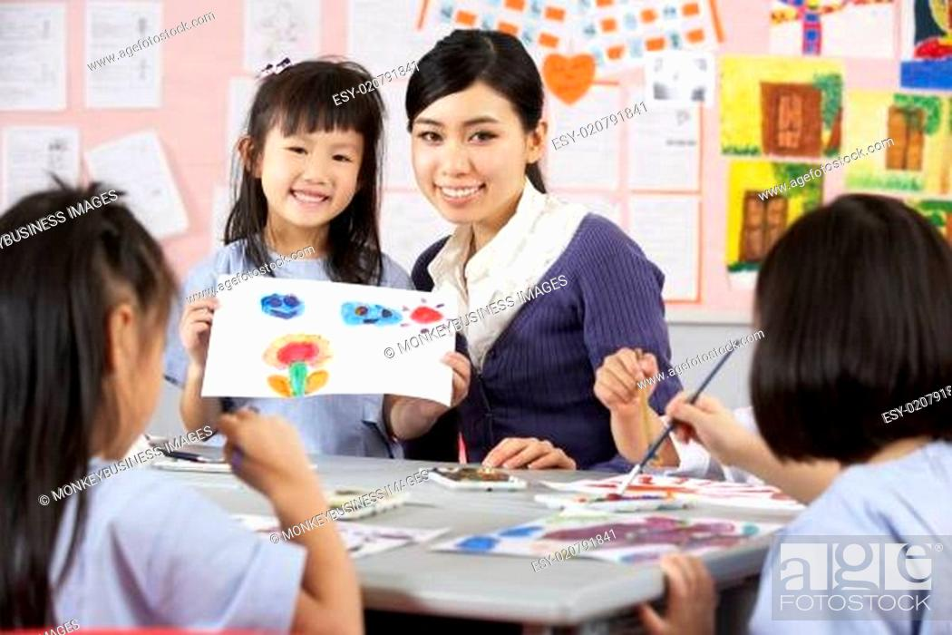 Photo de stock: Teacher Helping Students During Art Class In Chinese School Classroom.