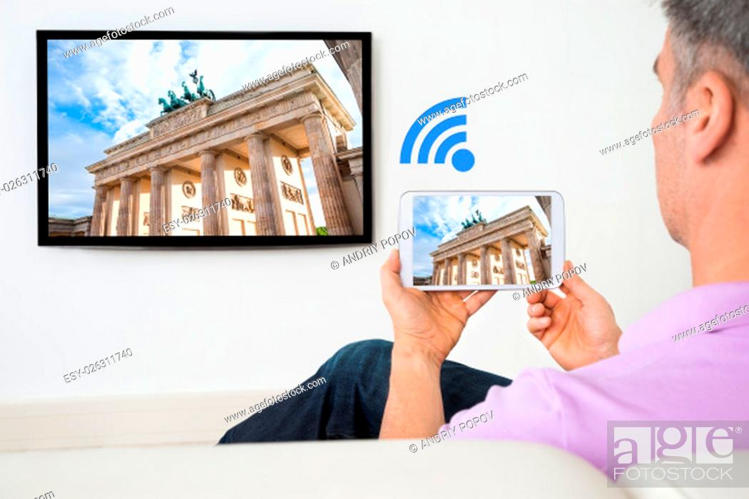 Stock Photo: Man Sitting On Sofa Holding Smartphone Connected To A TV.