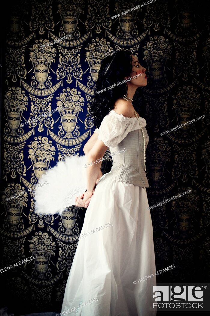 Stock Photo: young woman with long black hair wearing a long period white dress with corset holding an old period fan behind her back.