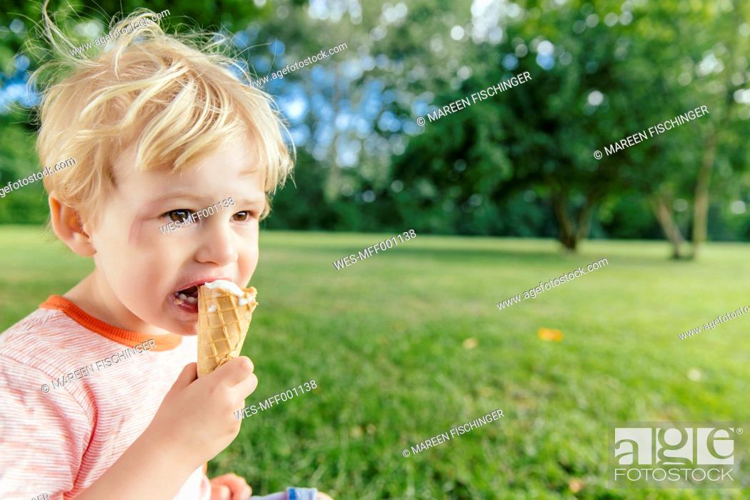 Stock Photo: Germany, North Rhine-Westphalia, Bonn, blonde male toddler eating icecream.