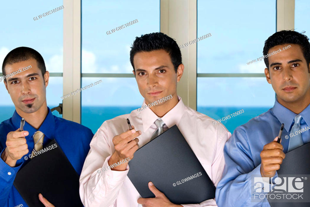 Stock Photo: Portrait of three businessmen holding pens.
