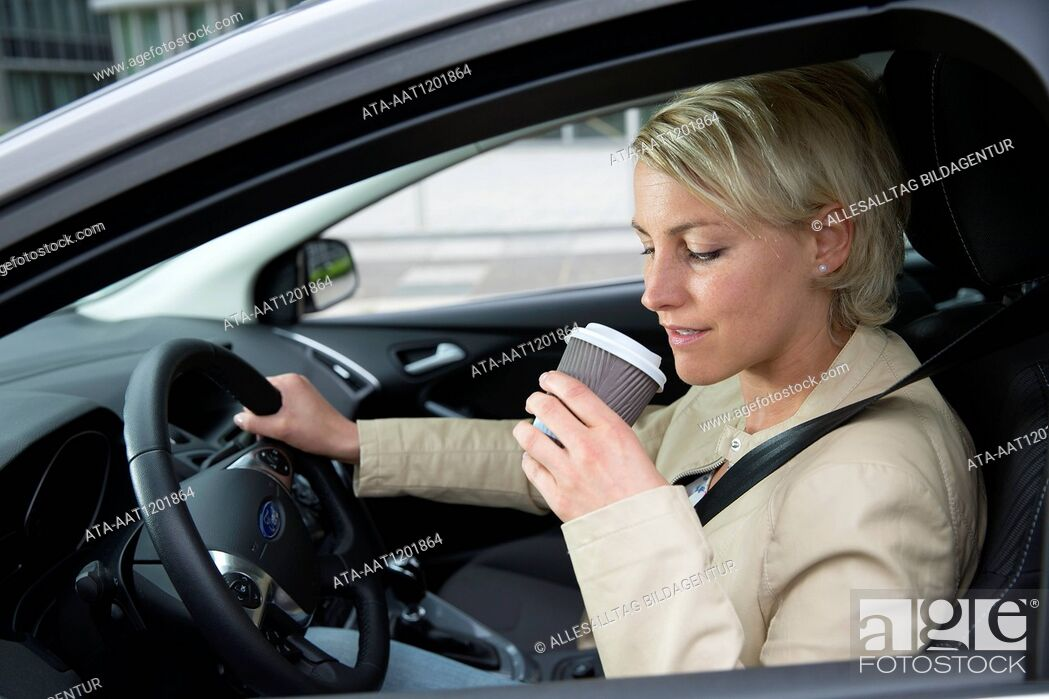 Stock Photo: Female car driver is drinking a coffee.