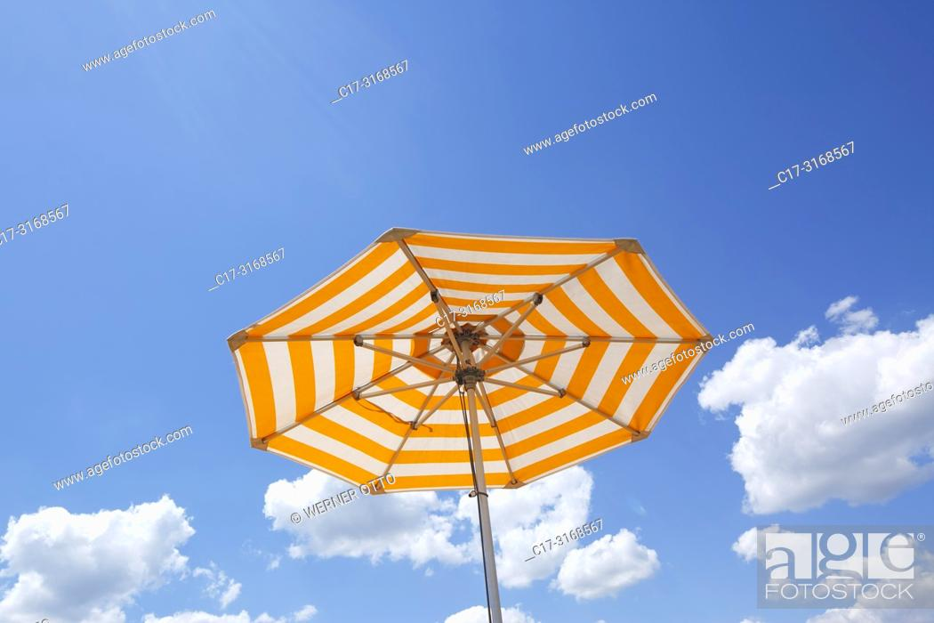 Imagen: one parasol on a cruise ship against the blue sky, yellow and white, cumulus clouds, holiday, freetime, recreation, relaxation, sunlight, sunshine.