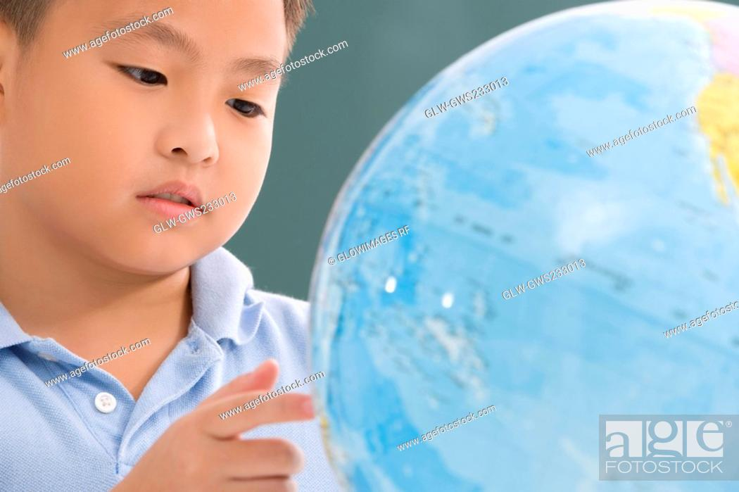 Stock Photo: Close-up of a boy looking at a globe.