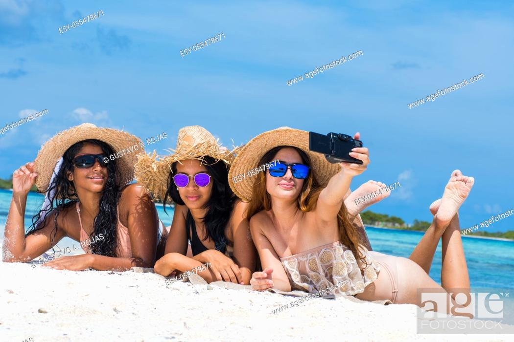 Stock Photo: Three happy girls friends in summer clothes taking a selfie at the beach.
