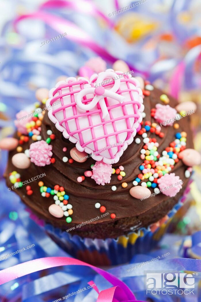 Stock Photo: A chocolate cupcake topped with a pink heart for a party.