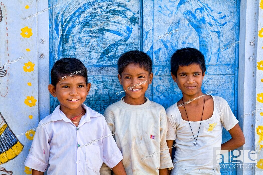 Stock Photo: Colorful children aged 6 and 7 against blue wall portrait in Jaipur Rajasthan India.