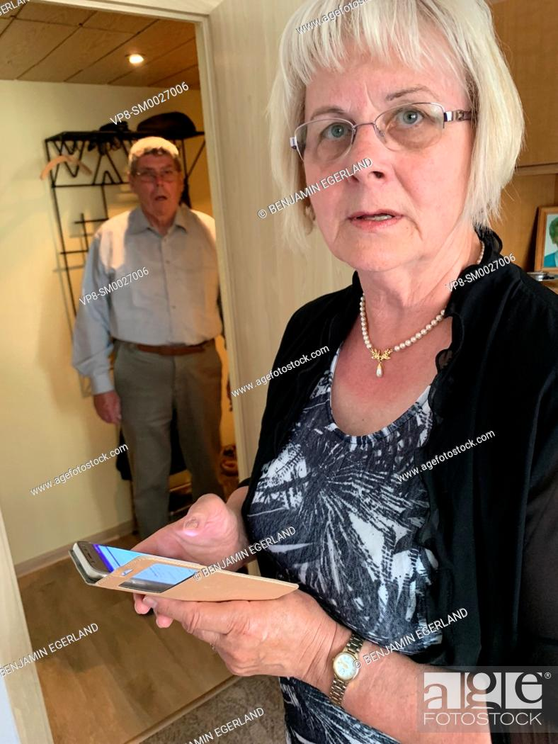 Stock Photo: confused senior woman holding smartphone at home next to baffled senior husband, in Cottbus, Germany.