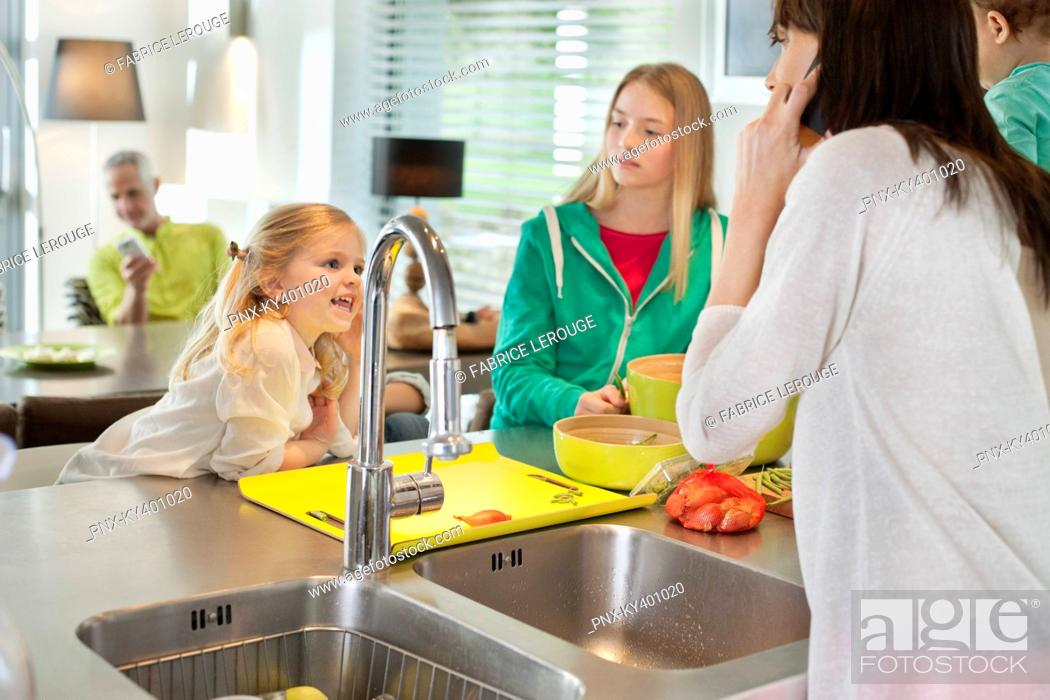 Stock Photo: Girls with her mother in a kitchen.