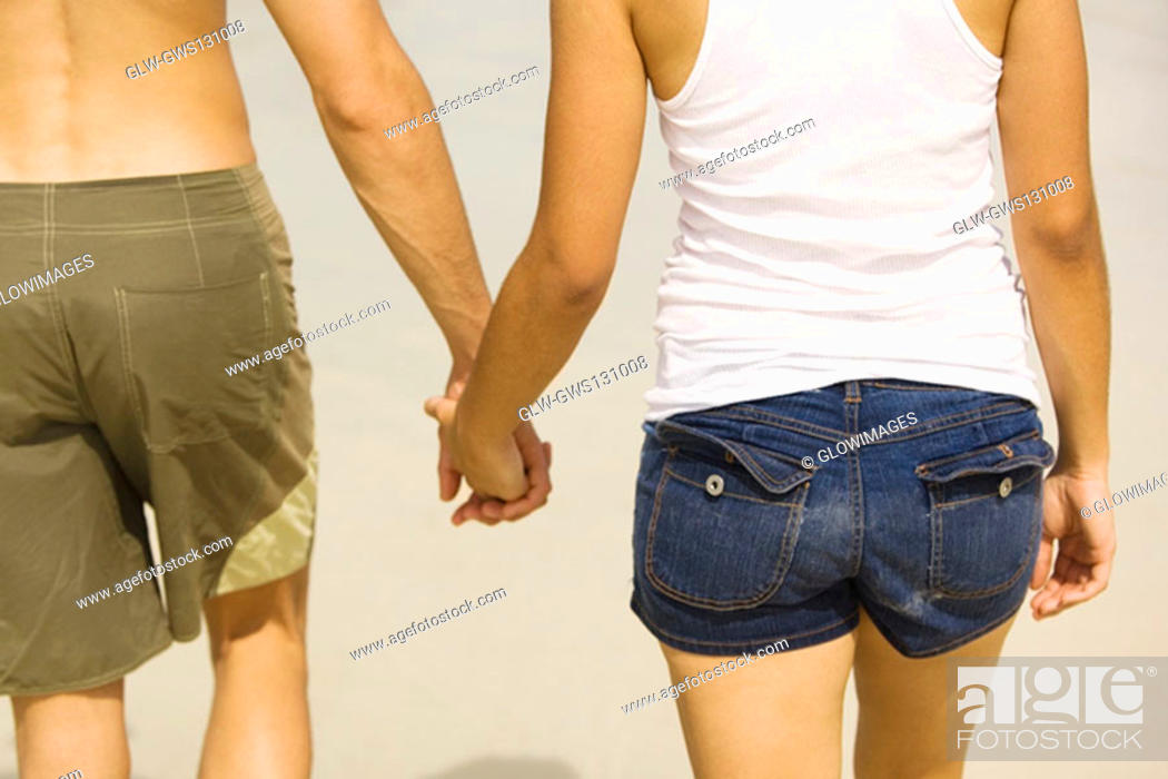 Stock Photo: Mid section view of a young man and a teenage girl holding hands.