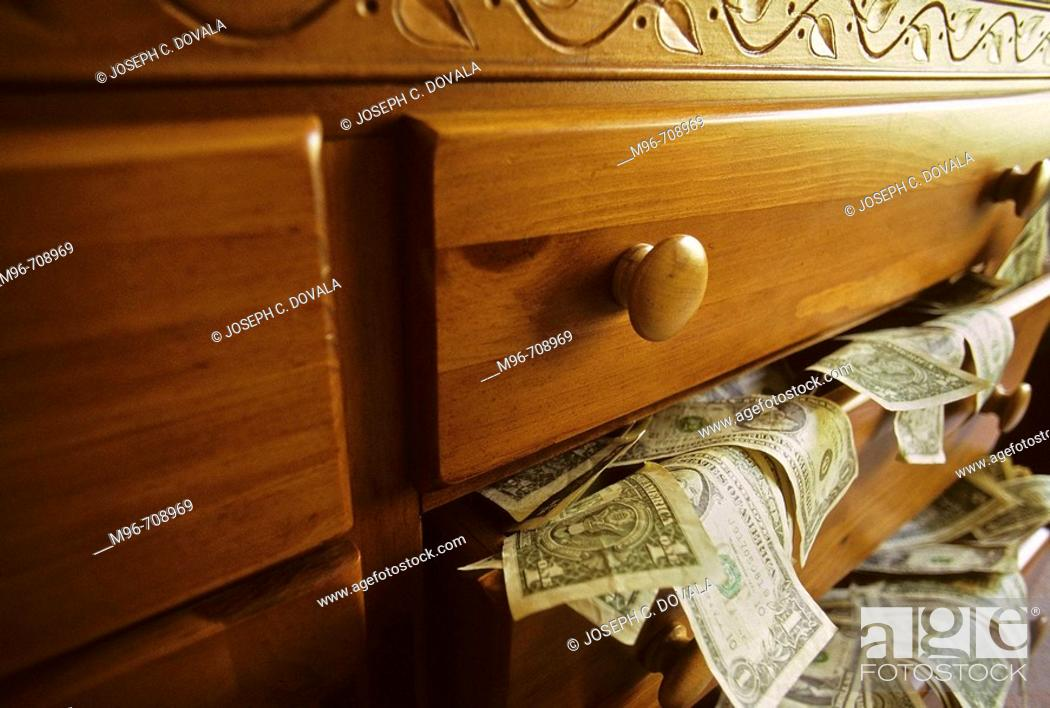 Stock Photo: USA money spilling out drawer.