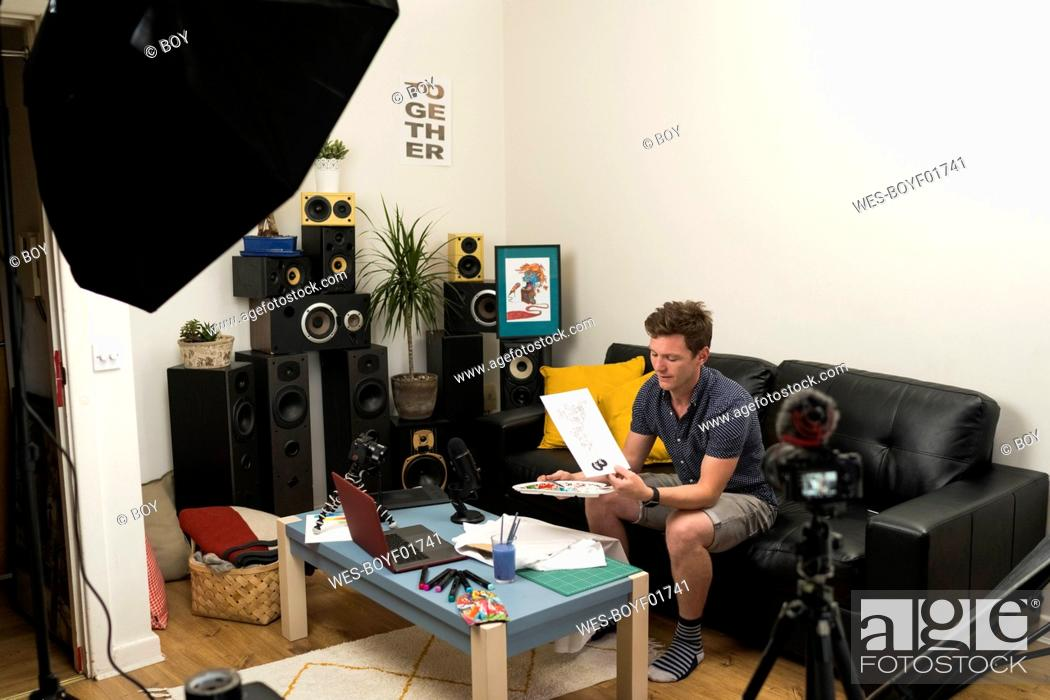 Stock Photo: Content creator showing doodle while live streaming on camera at home.