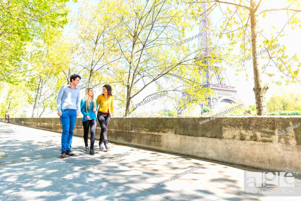 Stock Photo: Friends walking near eiffel tower, face to face smiling, Paris, France.