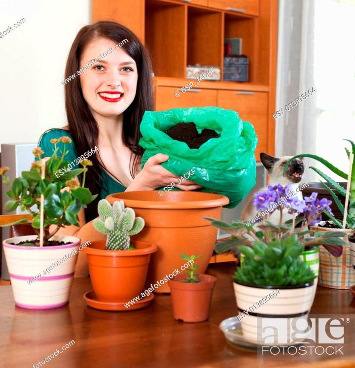 Stock Photo: Brunette girl transplanting potted flowers.