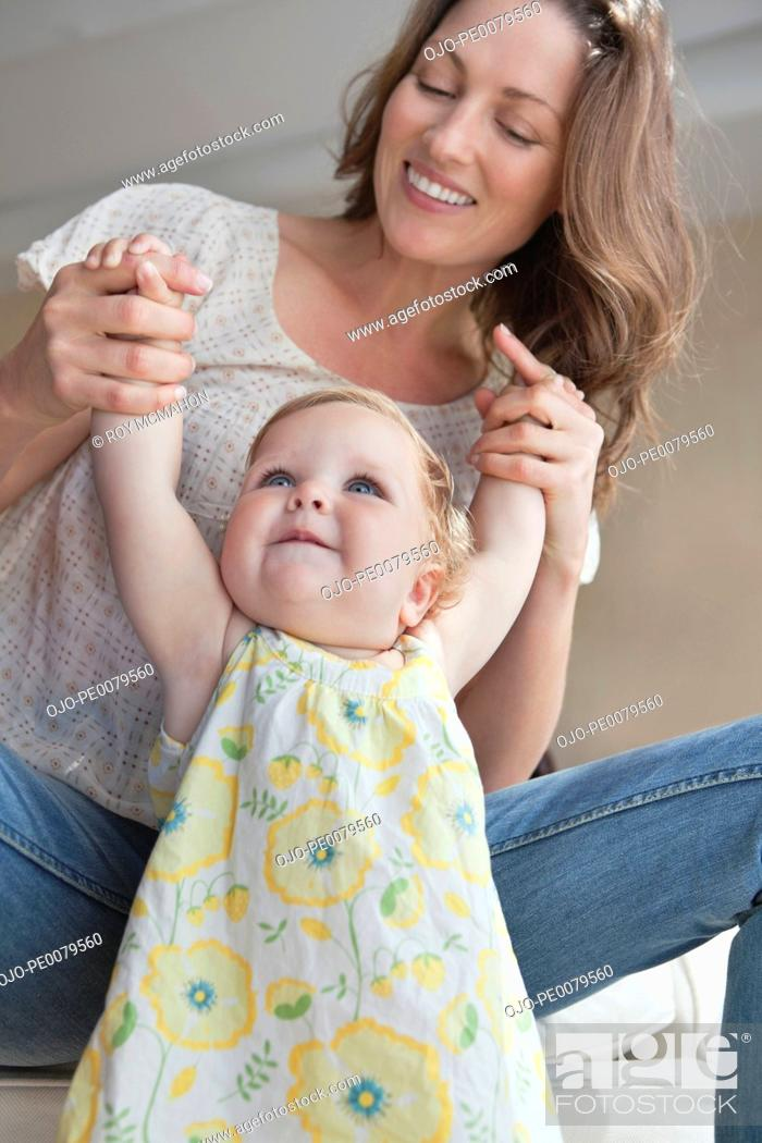Stock Photo: Mother holding hands with baby daughter.
