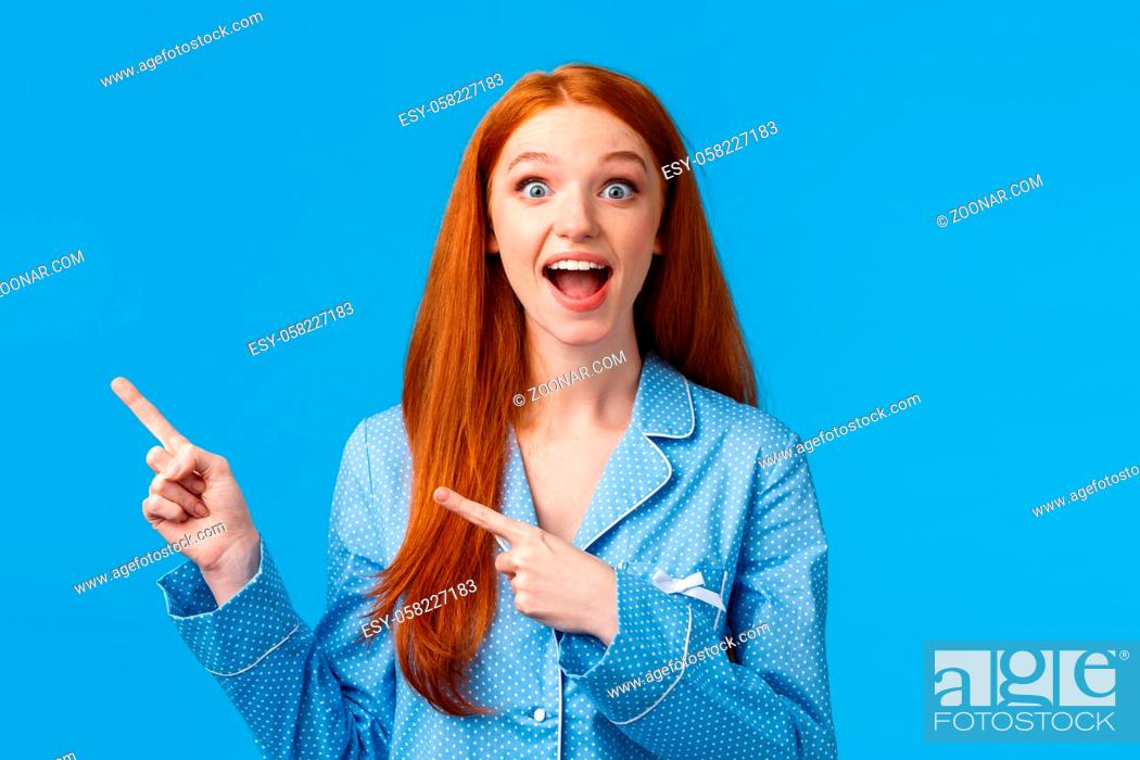 Stock Photo: Overwhelmed amused pretty redhead teen girl in nightwear screaming excited and amazed, pointing upper left corner, drop jaw gasping astonished.