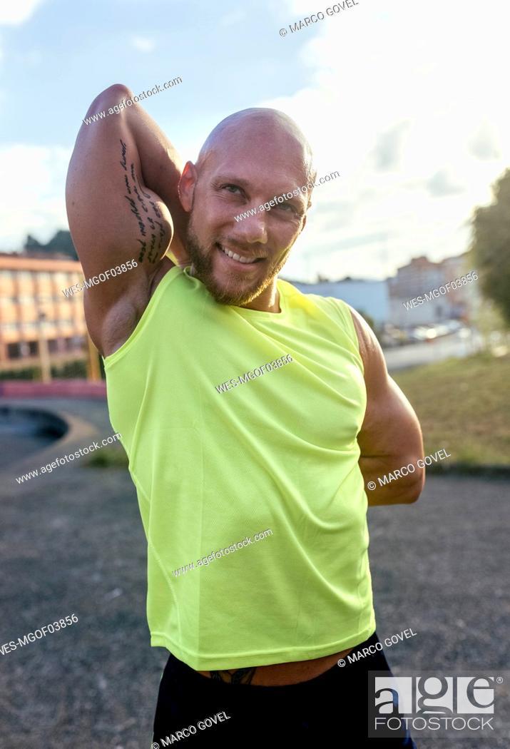 Photo de stock: Smiling muscular man stretching outdoors.