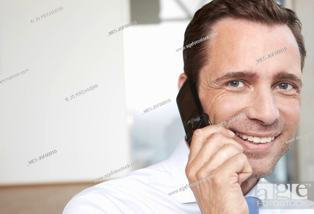 Stock Photo: Germany, Cologne, Businessman using mobile phone, smiling, portrait, close-up.