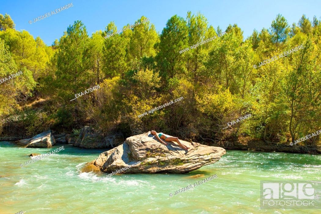 Imagen: Woman sunbathing on rock at river.