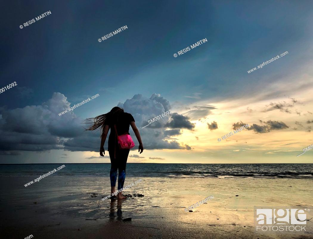 Stock Photo: Young teenage girl at the beach with sunset.