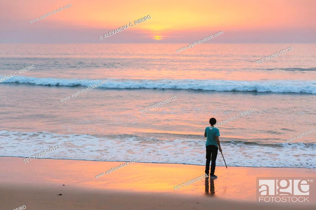 Imagen: Young man on beach at sunset in Lisbon, Portugal.