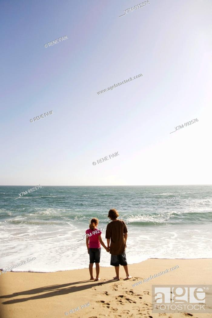 Stock Photo: Boy and girl looking out contemplatively at the vast ocean as the sun begins to set.