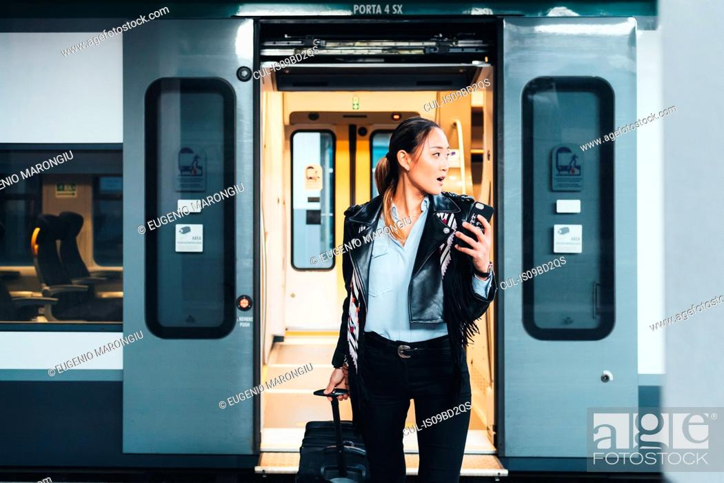 Stock Photo: Woman getting off train, pulling wheeled suitcase, holding smartphone.