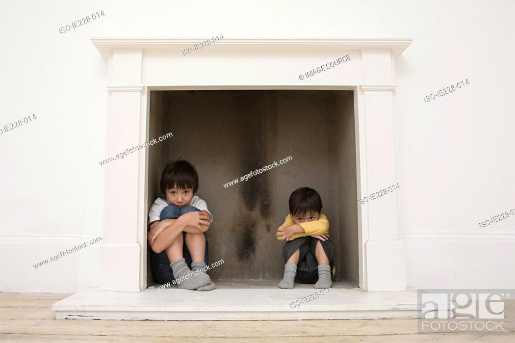 Stock Photo: Boys hiding in a fireplace.